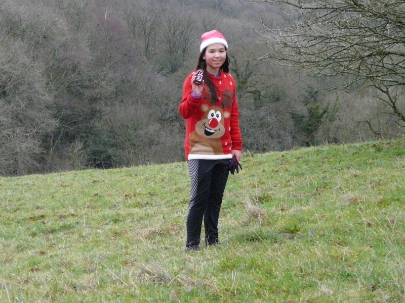 One of Santa's helpers waits patiently for the next passing runner